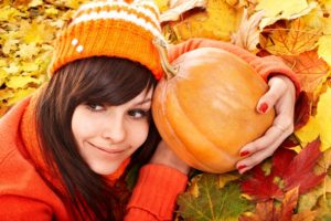 Happy young woman with  pumpkin on autumn leaves. Outdoor.